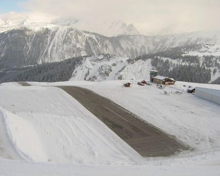 a frozen runway at courchevel airport surounded by snowy mountains