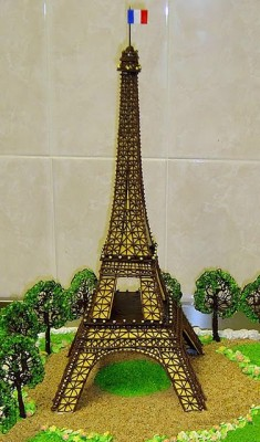a cake shaped as the Eiffel Tower with trees in the backround