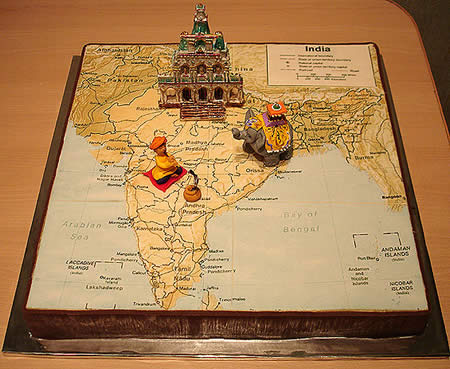 a cake shaped as the map of india with several 3d figures of an elephant and indian