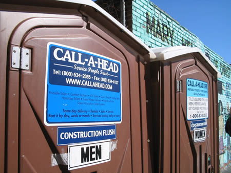 mens brown portable toilet with a call a head sign