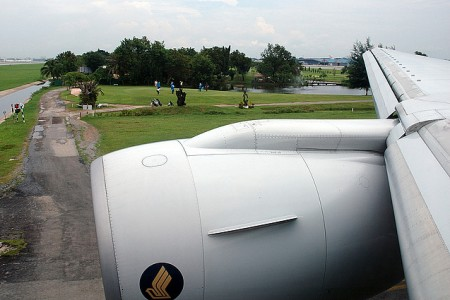 a view of a golf course from a plane window as the aircraft touches down at bangkok airport