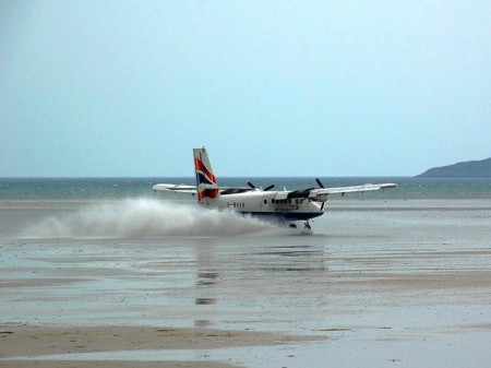 a small plane landing on a sandy beach in barra with sea water spraying up behind the aircraft