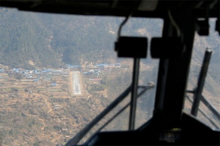 a view of lukla airport through the cockpit of an aproaching plane